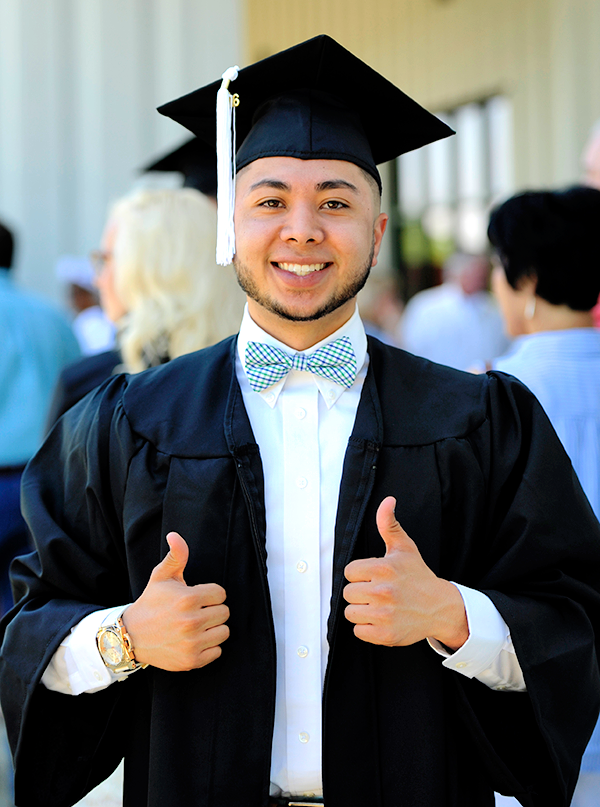Student in cap and gown giving the thumbs up signal.